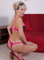 Older babe Nela bares her clothes to show off her mature ass while riding a dick on webcam