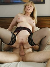 Nina Hartley uses her pair of big breasts to lure a younger guy into fucking her